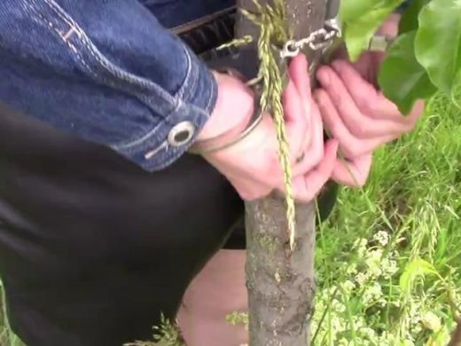 Am Baum mit Kapuze und mit Handschellen gefesselt
